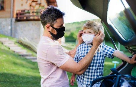 Padre con hijo pequeño viajando en coche, usando máscaras faciales .