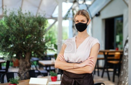 Photo for Portrait of waitress with face mask standing outdoors on terrace restaurant, arms crossed. - Royalty Free Image