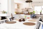 dining table with pine cones decoration and flowers on kitchen unfocused background