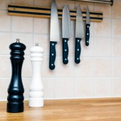 Black and white salt and pepper mill on wooden kitchen counter Top and kitchen knives