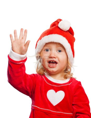 Photo for Cute caucasian girl in Santa's clothing waving her hand and looking into the camera isolated on white background - Royalty Free Image