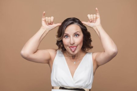 Funny adult woman making horns signs and showing stupid mimicry at camera on light brown background, Emotion and feeling concept