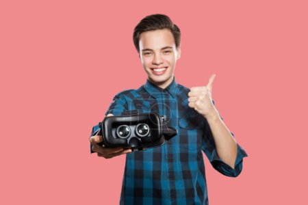satisfied young man with vr headset showing thumbs up and looking at camera on pink background