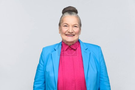 Photo for Cute woman wearing blue suit and pink shirt toothy smiling and looking at camera on gray background, Expression emotion and feelings concept - Royalty Free Image