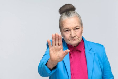 aged grandma wearing blue suit and pink shirt showing stop sign at camera on gray background, Expression emotion and feelings concept