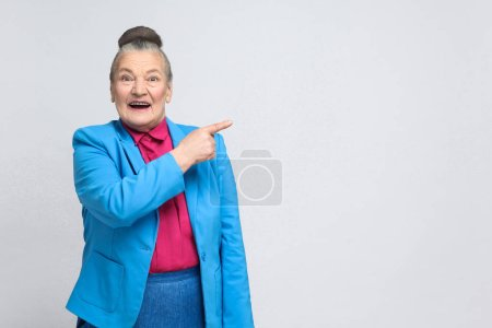 aged woman in blue suit and pink shirt pointing finger to right and toothy smiling, Emotion and feelings concept
