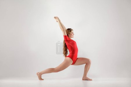 Side view of attractive athletic woman in red leotard doing crescent lunge yoga pose