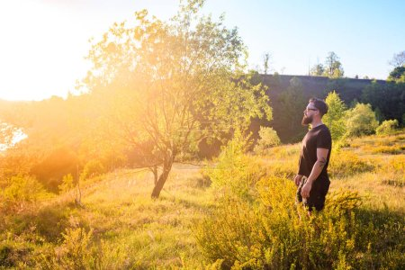 man standing on summer green hill with trees at sunny day