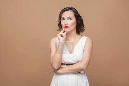 puzzled middle aged woman in white dress touching chin on brown background