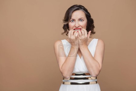Photo for Nervous woman in white dress biting nails with excitement and nervously looking at camera on brown background - Royalty Free Image