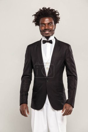 African well dressed man in classic style tuxedo smiling on gray background
