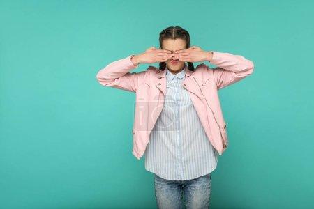 junge Frau mit Zopf-Frisur, die zeigt, dass ich es nicht sehen will Geste auf blauem Hintergrund