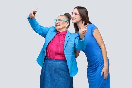 Photo pour Grand-mère heureuse avec petite-fille en robe bleue et costume posant et faisant selfie et souriant, concept de petite-fille avec relation grand-mère - image libre de droit