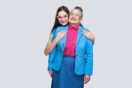 Photo pour Heureuse petite-fille satisfaite étreignant sa grand-mère et regardant la caméra avec un sourire de dents, concept de petite-fille avec relation grand-mère - image libre de droit