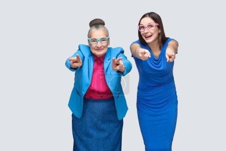 Photo pour Grand-mère heureuse avec petit-enfant pointant du doigt la caméra et souriant, concept de petite-fille avec relation grand-mère - image libre de droit
