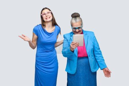 Photo pour Malheureux petite-fille femme debout près de femme âgée avec tablette PC sur fond gris, concept de relation dans la famille - image libre de droit