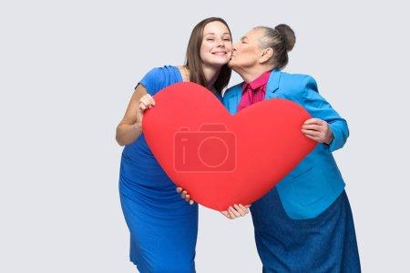 Photo pour Grand-mère embrasser petite-fille tout en tenant grande forme de coeur sur fond gris, Grand amour dans le concept de la famille - image libre de droit