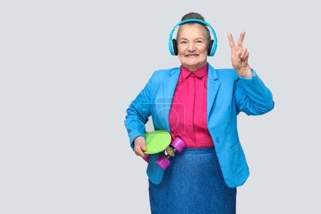 Grand-mère drôle branchée dans coloré style décontracté avec un casque bleu, écouter de la musique et en montrant le signe de la paix tout en tenant une planche à roulettes verte sur fond gris