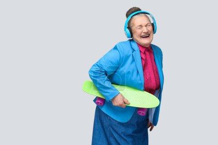 Trendy grand-mère joyeuse drôle dans coloré style décontracté avec un casque bleu, écouter de la musique et de rire avec les yeux fermés tout en tenant une planche à roulettes verte sur fond gris