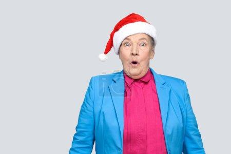 Grand-mère surprise en costume bleu et rouge bonnet debout et en regardant la caméra avec visage étonné et bouche ouverte et de grands yeux sur fond gris