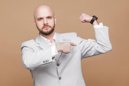 Photo pour Sérieux beau chauve d'âge moyen barbu homme d'affaires en costume gris clair regardant la caméra et montrant biceps sur fond brun - image libre de droit