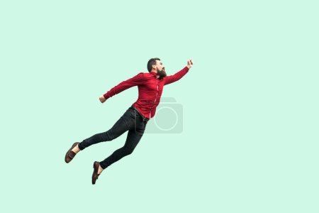 Photo for Strong bearded businessman felt himself superhero and flying up on light green background, Superman style, Enthusiasm concept - Royalty Free Image