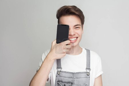 Portrait of funny handsome modern young man in denim overalls and white T-shirt holding and covering one eye with smartphone while looking at camera on grey background