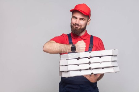 Young cheerful delivery man with beard in blue uniform and red t-shirt holding stack of cardboard pizza boxes on grey background