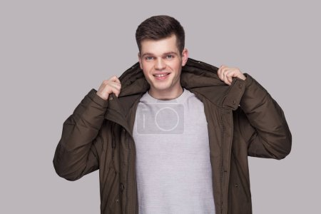 Photo for Portrait of young happy handsome man in light gray shirt and dark green parka looking at camera with toothy smile on gray background - Royalty Free Image