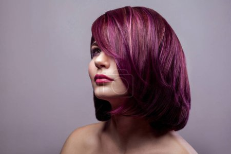 Portrait of beautiful fashion model woman with short purple colored hairstyle and makeup and looking away on gray background.