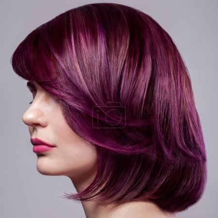 side view portrait of beautiful fashion model woman with short purple colored hairstyle and makeup on gray background.
