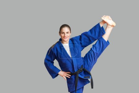 Beautiful happy athletic karate woman in blue kimono with black belt making vertical twine and looking at camera with toothy smile on gray background, Japanese martial arts concept