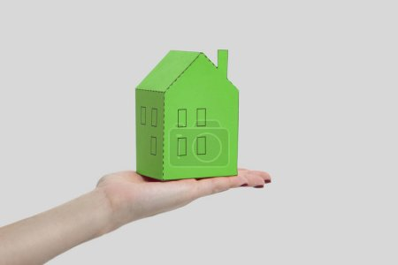 Photo for Female hand holding and showing green paper house model on gray background, mortgage concept - Royalty Free Image
