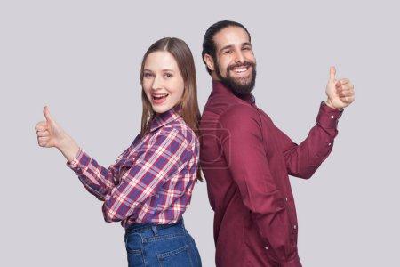 Photo pour Profil vue de côté de heureux satisfait barbu homme et femme dans un style décontracté en regardant la caméra et en souriant avec les pouces vers le haut sur fond gris - image libre de droit