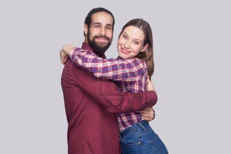Photo pour Portrait d'un homme et d'une femme barbus heureux et satisfaits dans un style décontracté s'embrassant et regardant la caméra avec un sourire de dents sur fond gris - image libre de droit