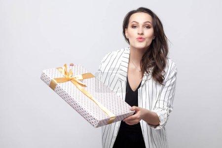 Photo pour Gentillesse belle jeune femme brune en manteau blanc debout et donnant cadeau avec arc jaune et envoyer de l'air tout en regardant la caméra sur fond gris - image libre de droit