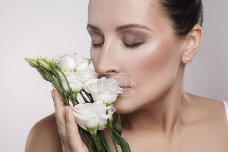 Photo for Portrait of mature woman with perfect skin and aged wrinkles leaning on flowers - Royalty Free Image