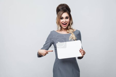 Photo for Portrait of happy beautiful modern woman in grey dress holding and pointing finger to say cloud on grey background - Royalty Free Image