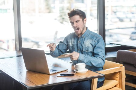 Photo for Angry upset bearded young big boss in blue jeans shirt sitting in cafe and making video call on laptop while pointing finger and blaming companion - Royalty Free Image