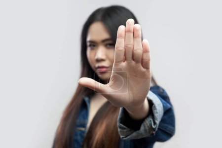 Photo for Serious beautiful brunette asian young woman in casual blue denim jacket standing with stop hand sign and looking at camera on light grey background. - Royalty Free Image