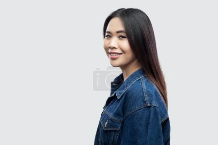 Photo for Portrait of glad beautiful brunette asian woman with makeup and straight dark hair looking at camera with toothy smile on light grey background - Royalty Free Image