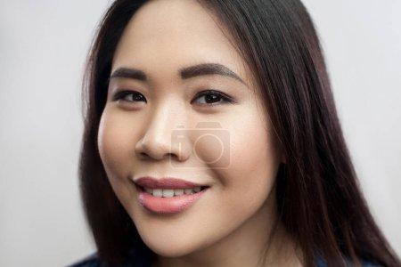 Photo pour Portrait d'heureuse belle femme asiatique brunette avec le maquillage et les cheveux tout droit noirs regardant la caméra avec pleines dents sourire sur fond gris clair - image libre de droit