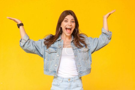 Photo for Portrait of surprised beautiful brunette  woman with makeup in denim casual style standing with raised arms and looking at camera with excited face on yellow background. - Royalty Free Image