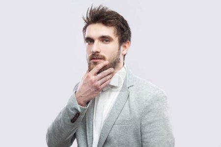 Photo pour Portrait d'un bel homme barbu et sérieux en chemise blanche et costume gris décontracté touchant le visage et regardant la caméra sur fond gris clair . - image libre de droit