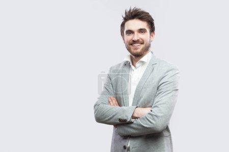 Photo pour Portrait d'un bel homme barbu heureux et satisfait en chemise blanche et costume gris décontracté debout avec les mains croisées et regardant la caméra avec le sourire des dents sur fond gris clair - image libre de droit