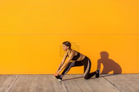 Photo for Side view of young beautiful sporty yogi woman in black sportswear stretching on street floor while standing on knee against orange wall background, sport and healthy concept - Royalty Free Image