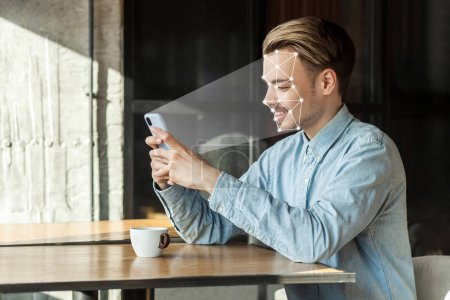 Photo pour Jeune homme heureux visage numérisation avec système de reconnaissance faciale sur smartphone et assis dans le café, Mobile biométrique identification et vérification visage concept de détection - image libre de droit