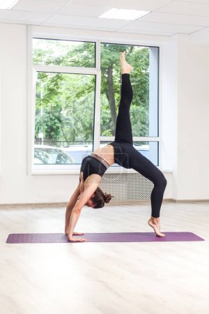 Photo for Side view of beautiful young woman wearing in black pants and top practicing yoga and standing in bridge exercise while doing one legged wheel pose at studio - Royalty Free Image