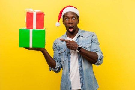 Photo pour Homme beau choqué en santa chapeau et chemise décontractée en denim debout avec bouche ouverte et pointant vers des boîtes-cadeaux à portée de main sur fond jaune - image libre de droit