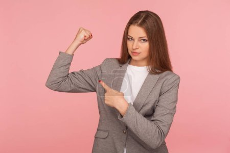 Photo for Portrait of ambitious self-confident young woman in business suit raising hands proudly pointing at biceps, feeling power, female strength, rights and feminism concept. indoor studio shot, isolated - Royalty Free Image